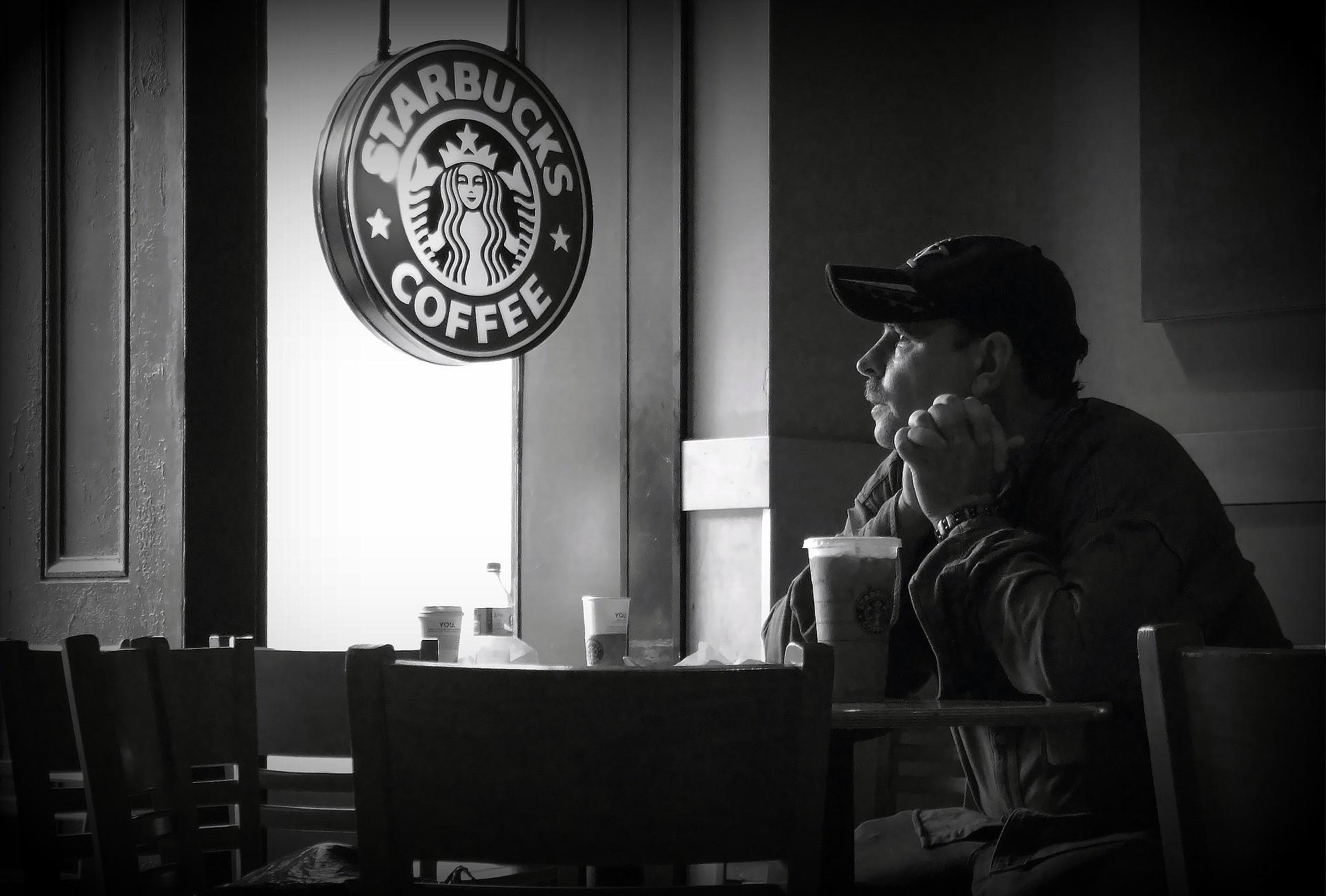 Señor bebiendo un café en cafetería StarBucks
